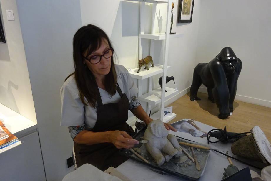 Chantal Porras sculpte en direct un ourson à partir d'un bloc de terre.