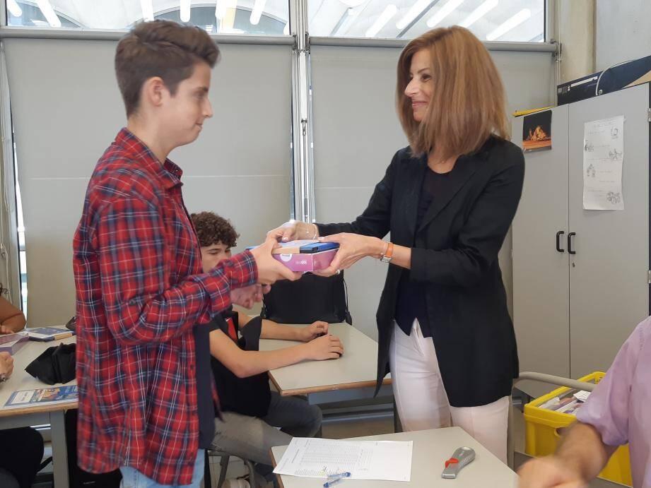 Un élève de seconde reçoit sa tablette des mains de la conseillère régionale Catherine Roubeuf.