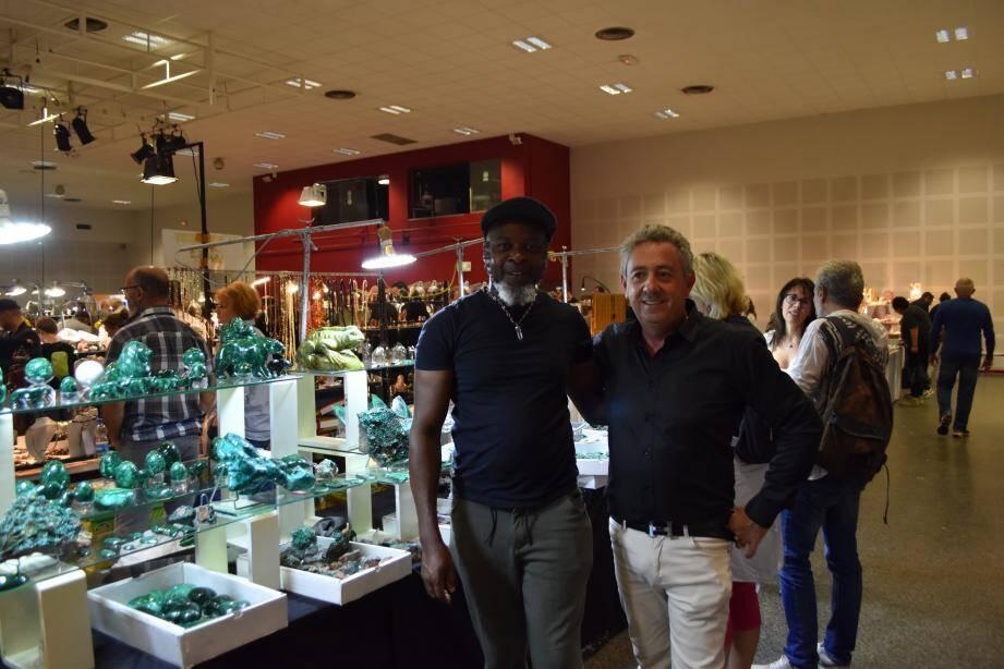 A droite, le président de l'Institut du monde minéral, Jean-Marie Hahn, aux côtés d'un exposant, François Wenge et ses pierres du Congo (malachite) aux nombreuses vertus.