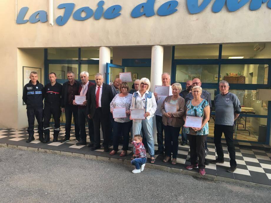 Avec les représentants de la municipalité, les seniors affichent fièrement leur certificat devant le local de « La Joie de vivre ».