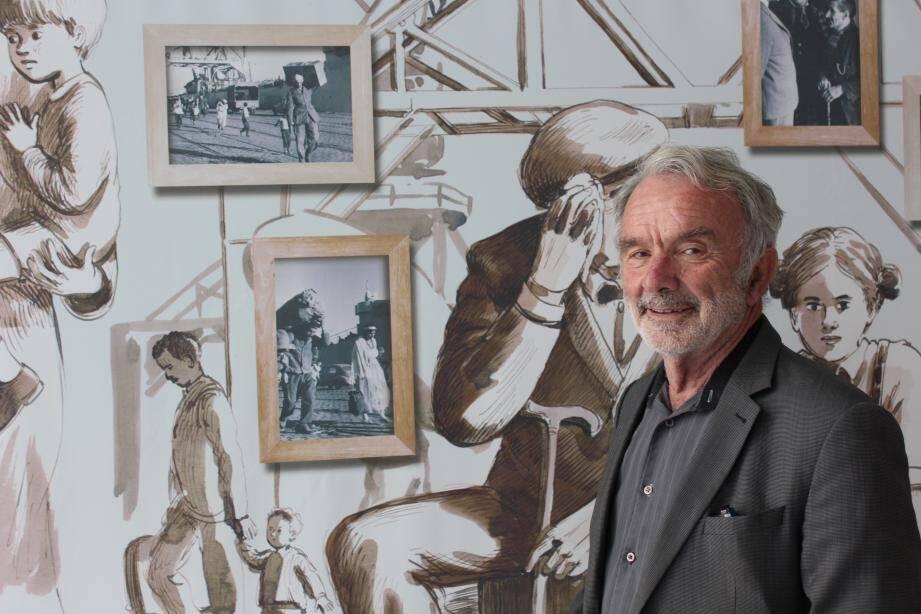 Joseph Perez devant la fresque des rapatriés et des photos d'arrivées à Toulon. Le centre possède également des archives de journaux, des objets et des maquettes.