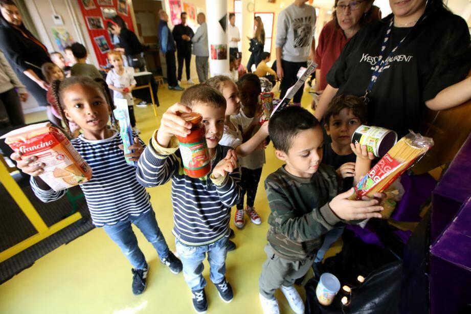 Farine, pâtes, sauces mais aussi brosses à dents et couches pour bébés, les enfants du centre de loisirs Jules-Ferry déposent avec enthousiasme les denrées dans leur boîte fabriquée pour l'occasion.
