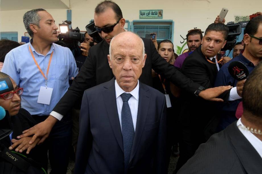 Le candidat à la présidentielle  Kaïs Saied quitte le bureau de vote après avoir déposé son bulletin dans l'urne, lors du second tour, le 13 octobre 2019 à Tunis