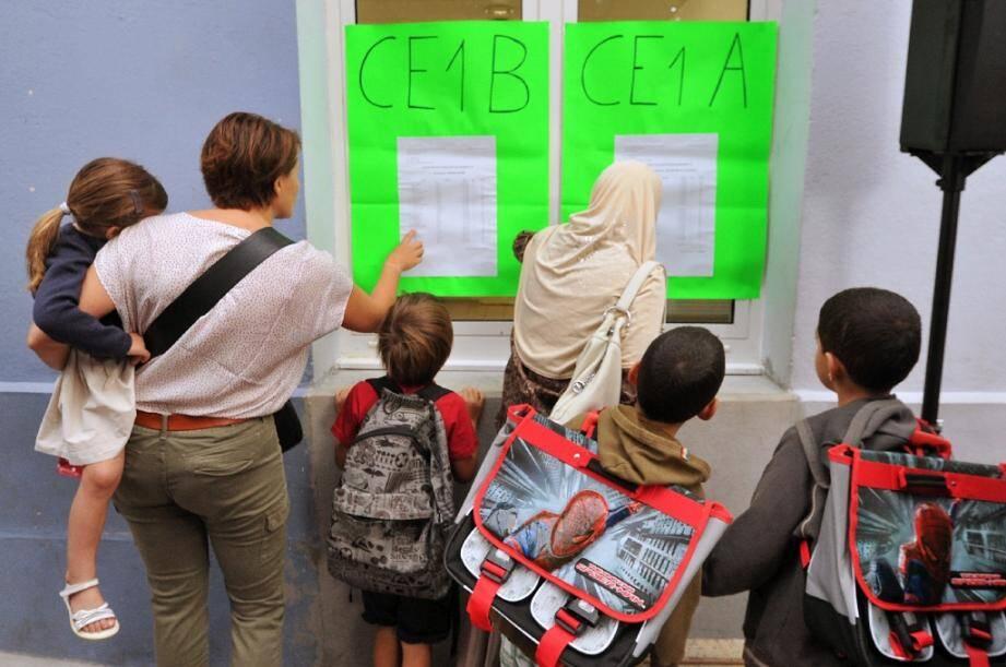 Des parents accompagnant leurs enfants regardent la liste des élèves par classe le jour de la rentrée, le 4 septembre 2012 à Bordeaux