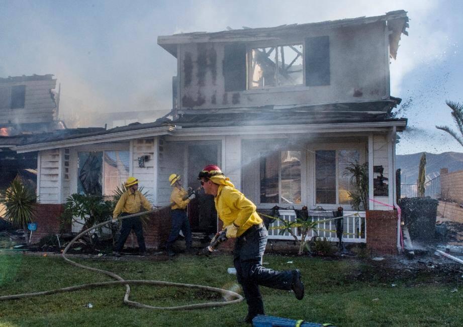 Des pompiers devant une maison touchée par le Tick Fire, près de Santa Clarita, en Californie, le 25 octobre 2019