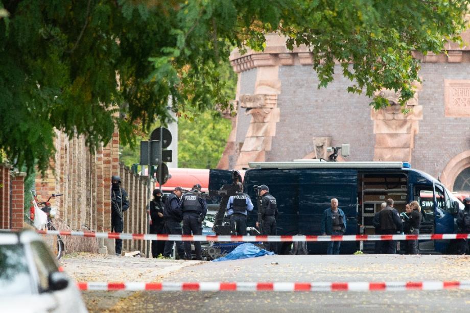 Des policiers allemands à côté du corps recouvert d'une victime, après une tentative d'assaut contre une synagogue à Halle (est) le 9 octobre 2019.