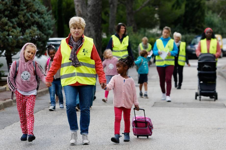 Un kilomètre à pieds, ça use, ça use. Un kilomètre à pieds, ça use les souliers.» Voilà ce que pourraient chanter les élèves des écoles L'Orée du bois et Louis-Clément le matin. Ils se rendent en marchant dans leur établissement comme des milliers de petits Français. Sauf qu'eux – c'est plus rare –, ils utilisent un pédibus. Un dispositif de ramassage scolaire, apparu à la fin des années 1970 au Danemark. Au lieu de s'asseoir dans un bus, on marche d'arrêt en arrêt! Du côté de Saint-Mandrier, l'initiative existe depuis octobre 2003.Un mardi matin sur les hauteurs du village, au niveau de l'ancienne gendarmerie, route du cap Cépet, il ne fait pas bien chaud. Le début du mois de novembre est plutôt humide. Ça n'a pourtant pas découragé Louisa et Clovis qui attendent, cartables sur le dos, à l'arrêt de pédibus avec quelques camarades. Ils retrouvent rapidement des bénévoles de l'APE (Association pour la protection de l'environnement) reconnaissables de loin à leur gilet jaune fluo. Ce sont les conducteurs du «bus» sans roues! Colette ou encore Marie-Ange encadrent les enfants, tout comme plusieurs mamans. Le petit cortège va traverser les résidences et faire deux ou trois arrêts (selon les inscrits) jusqu'à leur arrivée à l'école Louis-Clément prévue une vingtaine de minutes plus tard.Dans le rang, ça discute beaucoup! Entre enfants, entre adultes, entre enfants et adultes. La marche n'entame pas leur enthousiasme à se retrouver un peu avant l'heure de la sonnerie. Si l'APEs'est lancée dans l'aventure il y a près de quinze ans, c'est pour deux raisons principales, assure Marie-Anne Denans, une bénévole en charge de Marchons vers l'école.«un petit moment sportif»«D'abord, pour des motifs écologiques bien sûr. Cela évite de prendre la voiture pour de si petites distances. Mais aussi pour créer du lien social. Cela permet aux participants de faire connaissance.» À ses côtés, la maman de Clovis et Louisa, elle aussi «marcheuse» accompagnatrice, opine du chef. «C'est la pre
