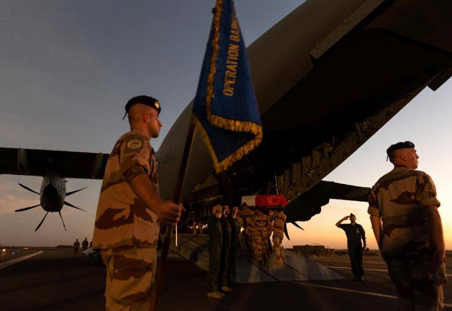 Les cercueils recouverts du drapeau aux couleurs de la France, près d'un soldat brandissant un étendard portant la mention