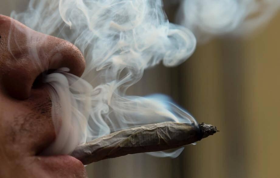 Un homme fumant un joint de cannabis.