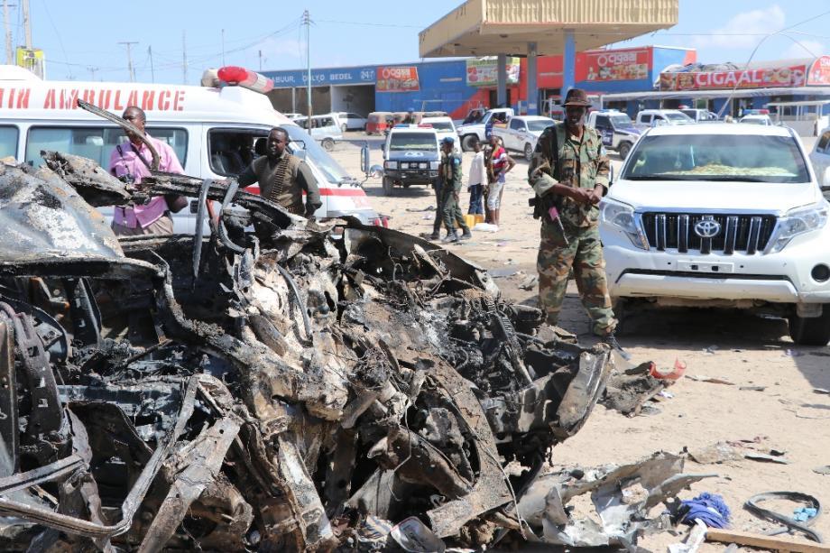 Un soldat se tient près de la carcasse d'une voiture détruite par un attentat qu a fait au moins 76 morts le 28 décembre 2019 à Mogadiscio.