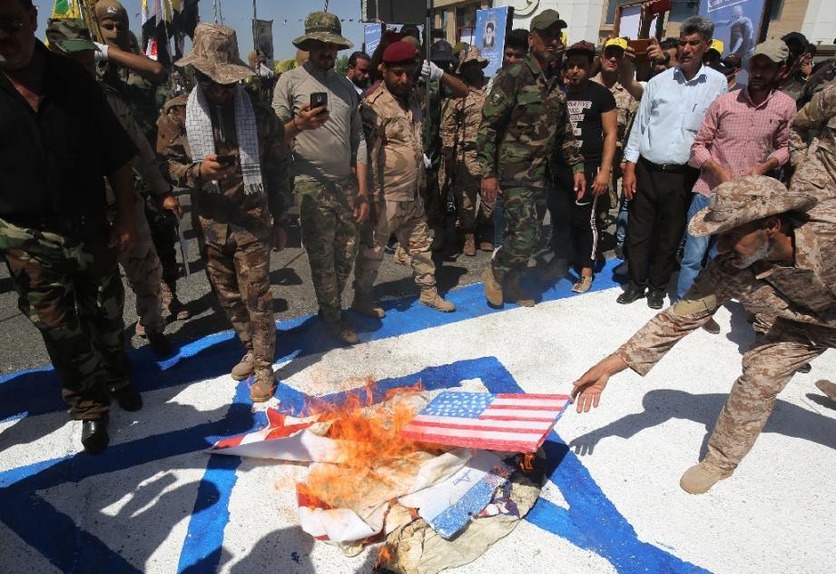 Sur cette photo d'archive, des combattants chiites irakiens des brigades du Hezbollah brûlent des drapeaux américains et israéliens durant un défilé militaire à Bagdad, le 31 mai 2019