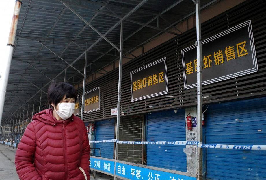 Une femme devant le marché aux poissons de Huanan, où un homme est décédé des suites de complications respiratoires avait acheté des victuailles.