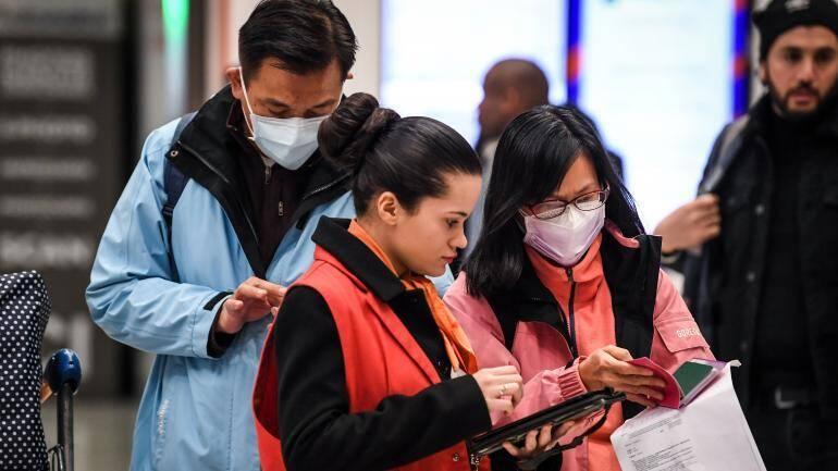 Une employée des Aéroports de Paris aide des passagers qui viennent de Chine, le 26 janvier 2020 à l'aéroport de Roissy-Charles de Gaulle.