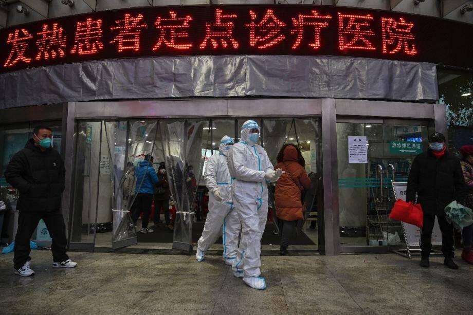Du personnel médical en combinaison de protection devant l'entrée de l'hôpital de la Croix-Rouge, le 25 janvier 2020 à Wuhan, épicentre du nouveau coronavirus en Chine