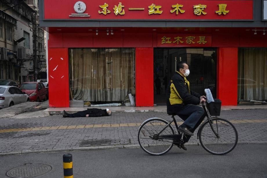 Un cycliste passe à côté du corps d'un homme mort dans la rue à Wuhan, le 30 janvier 2020 en Chine