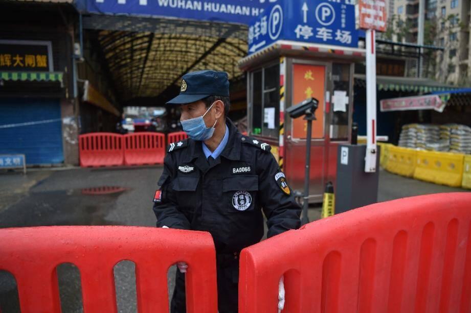 Un policier en faction devant le marché aux fruits de mer de Wuhan qui a été fermé après la découverte de cas d'infection à un coronavirus, le 24 janvier 2020 en Chine.