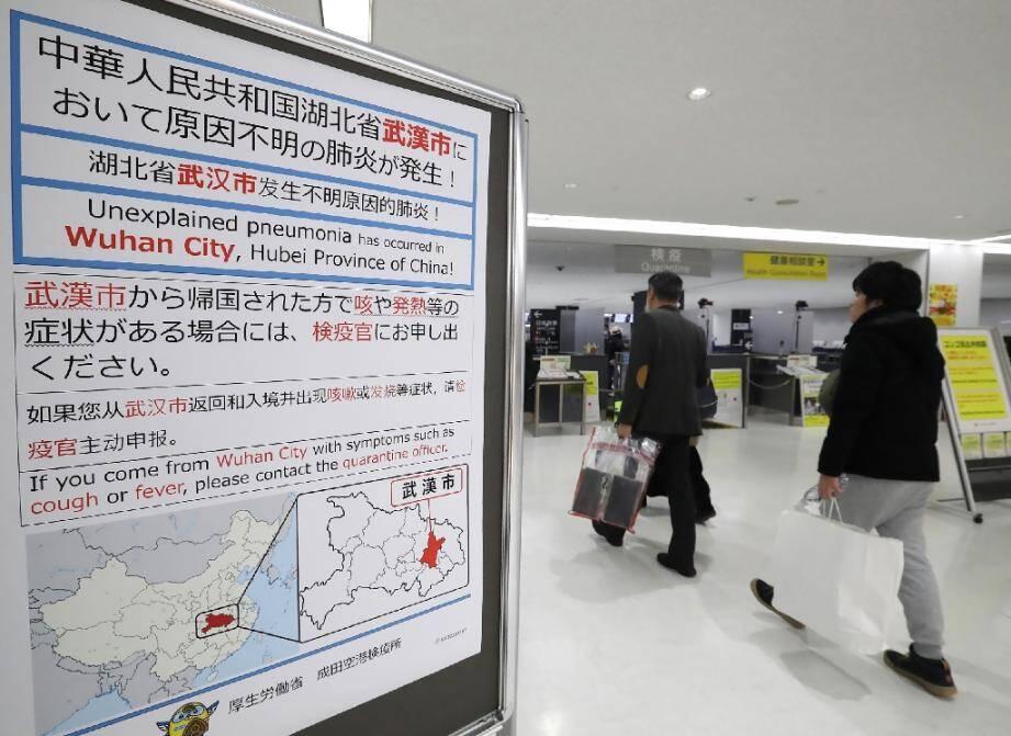 Des voyageurs devant un panneau alertant sur le coronavirus apparu en Chine, le 16 janvier 2020 à l'aéroport de Narita, au Japon