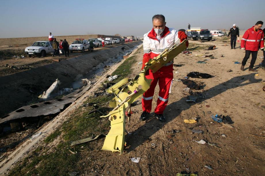 Un secouriste ramasse les débris de l'appareil qui s'est écrasé à Téhéran, tuant toutes les personnes à son bord.