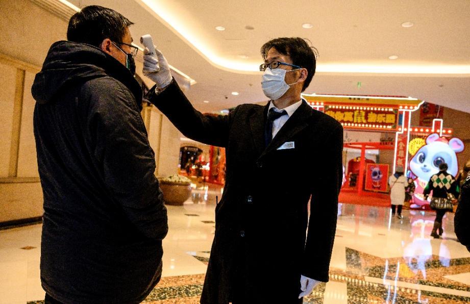 Un agent de sécurité prend la température d'un homme à l'entrée d'un centre commercial à Shanghai, le 8 février 2020.