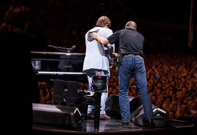 Elton John sur la scène d'Auckland, soutenu par un technicien.