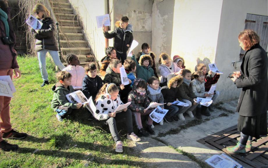 Les écoliers, attentifs aux explications d'Anne Mandrou, apprennent l'histoire de la voie ferrée et de la gare de Rians.
