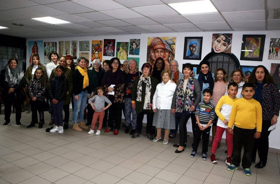 Devant les tableaux, les participantes à l'atelier de peinture, avec les enfants et  leur professeure Latifa Romé.