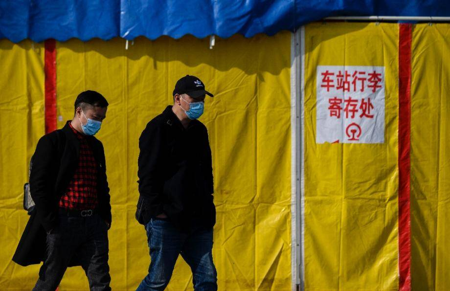 Deux hommes portant des masques de protection contre le coronavirus marchent dans une rue de Jiujiang, le 19 mars 2020 en Chine