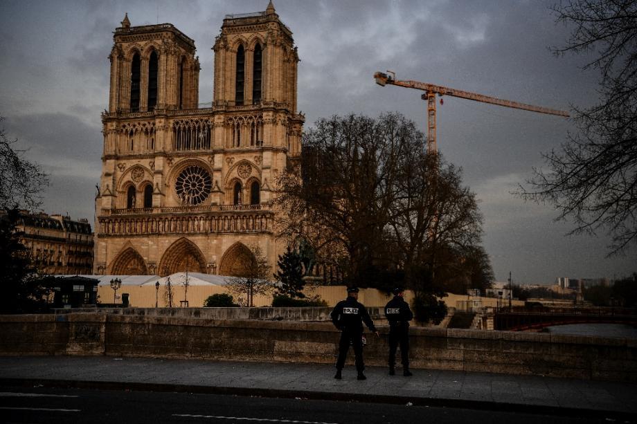 Des policiers patrouillent aux abords désertés de la cathédrale Notre-Dame de Paris, habituellement peuplés de touristes, le 17 mars 2020