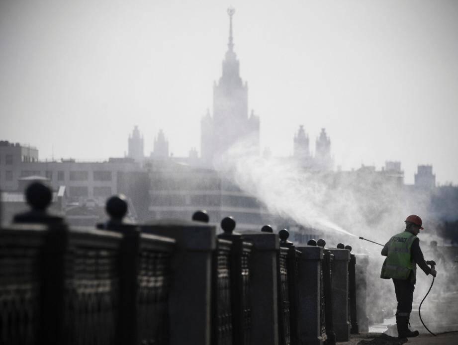 Un agent municipal désinfecte les bords des quais à Moscou, devant l'université d'Etat, le 28 mars 2020