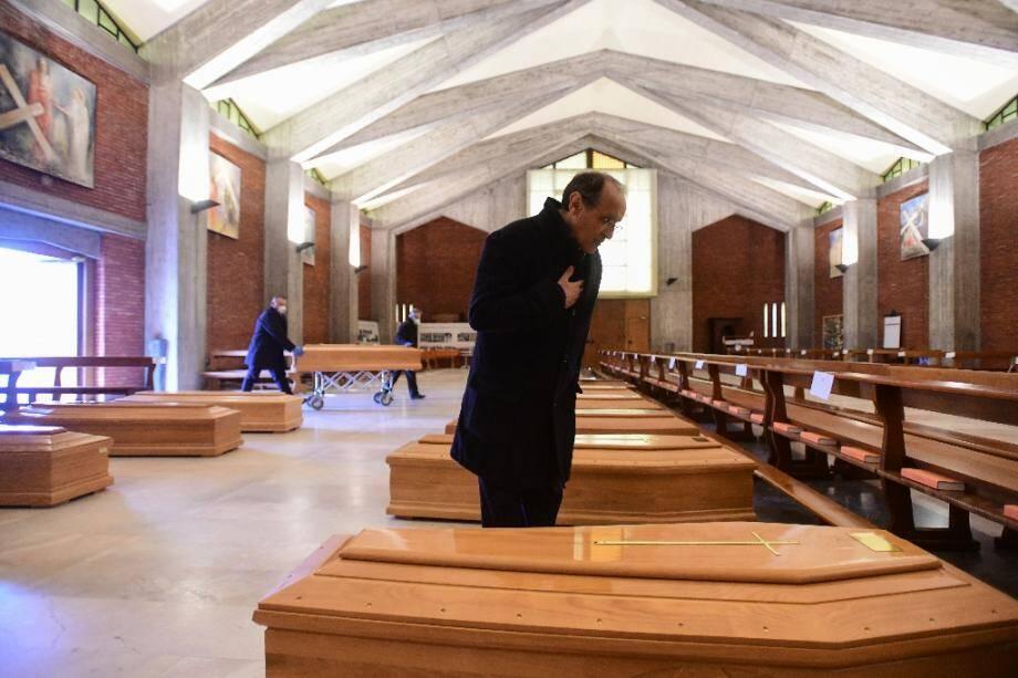 Le prêtre de la paroisse de Seriate, Don Mario, s'incline devant l'un des cercueils entreprosés dans l'église de sa commune, située près de Bergame, dans le nord de l'Italie, le 26 mars 2020