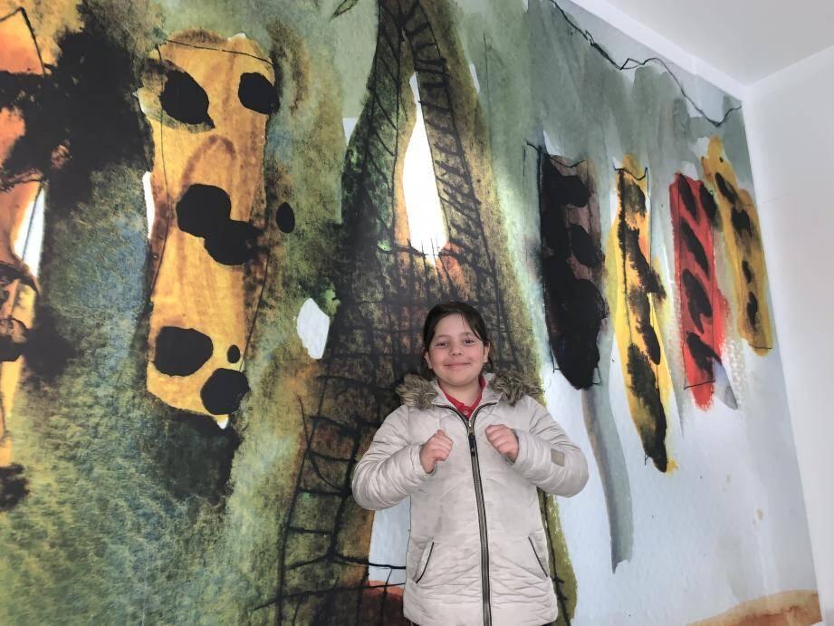 Juliette Sembolini, 9 ans, pose tout sourire devant son tableau.