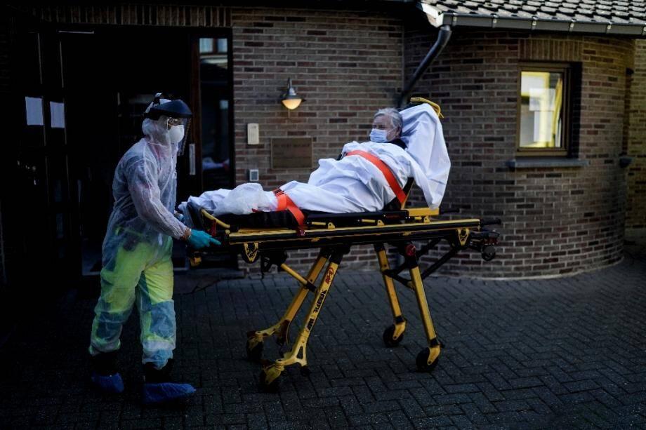 Un pompier en combinaison de protection transporte sur une civière une femme présumée atteinte par le Covid-19, le 10 avril 2020 à Liège, en Belgique