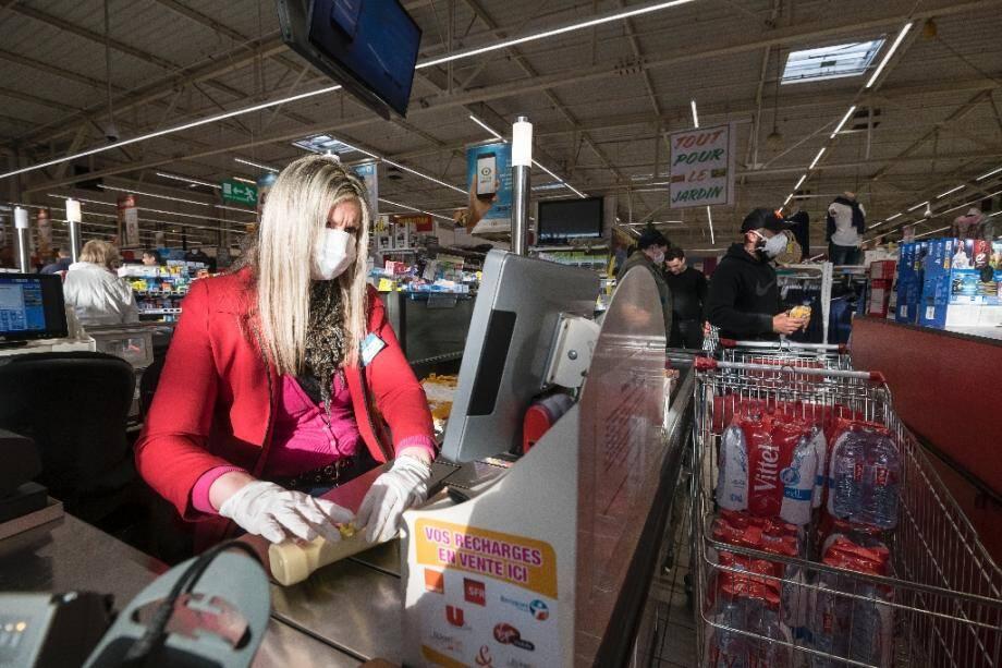 Une caissière porte un masque de protection dans un supermarché de Pfastatt, le 16 mars 2020 dans le Haut-Rhin