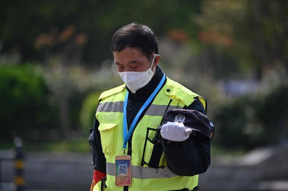 Un policier se fige lors des 3 minutes de silence en mémoire des morts du Covid-19, le 4 avril 2020 à Wuhan