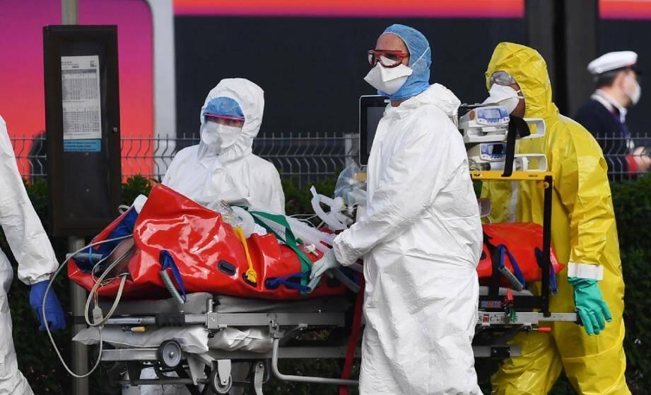 Des personnels soignants acheminent la civière d'un patient infecté par le Covid-19 de la gare d'Austerlitz à destination de Quimper, le 5 avril 2020