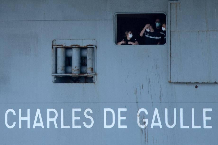 Le Charles de Gaulle avec des marins portant des masques arrive en rade Toulon, le 12 avril 2020