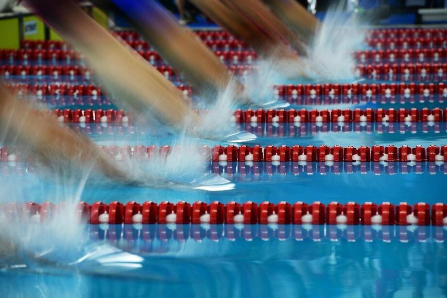 Des nageurs plongent lors des séries du 400 m quatre bages des Jeux asiatiques 2018 le 22 août 2018 à Jakarta.