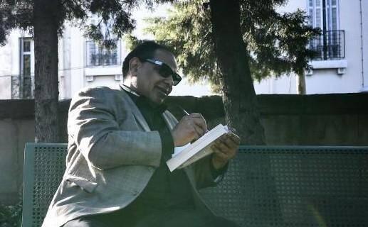 """L'écrivain égyptien Alaa el Aswany sur un banc des jardins de l'institut """"Imera"""" de l'Université d'Aix-Marseile."""