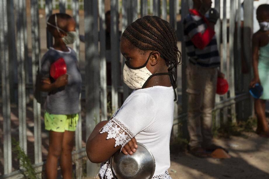 Des enfants font la queue, masqués, dans une école à Langa, près du Cap, pour recevoir un repas, le 14 mai 2020