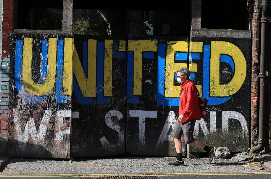 """Un homme passe devant un message peint sur un mur """"Nous restons unis"""", le 2 mai 2020 à Leeds, au Royaume-Uni"""