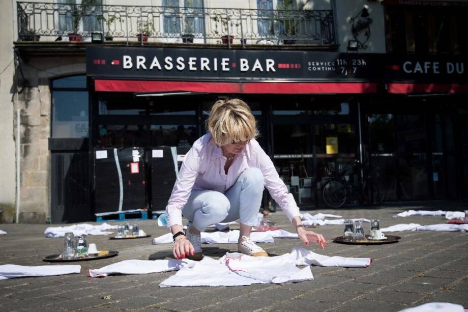Une femme étale des dizaines de blouses blanches, toques et plateaux sur une place face à un restaurant à Nantes, ouest, le 27 mai 2020, pour protester contre les conséquences du confinement