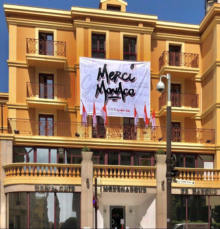 """La façade de la CMB arborant l'affiche """"Merci Monaco""""."""