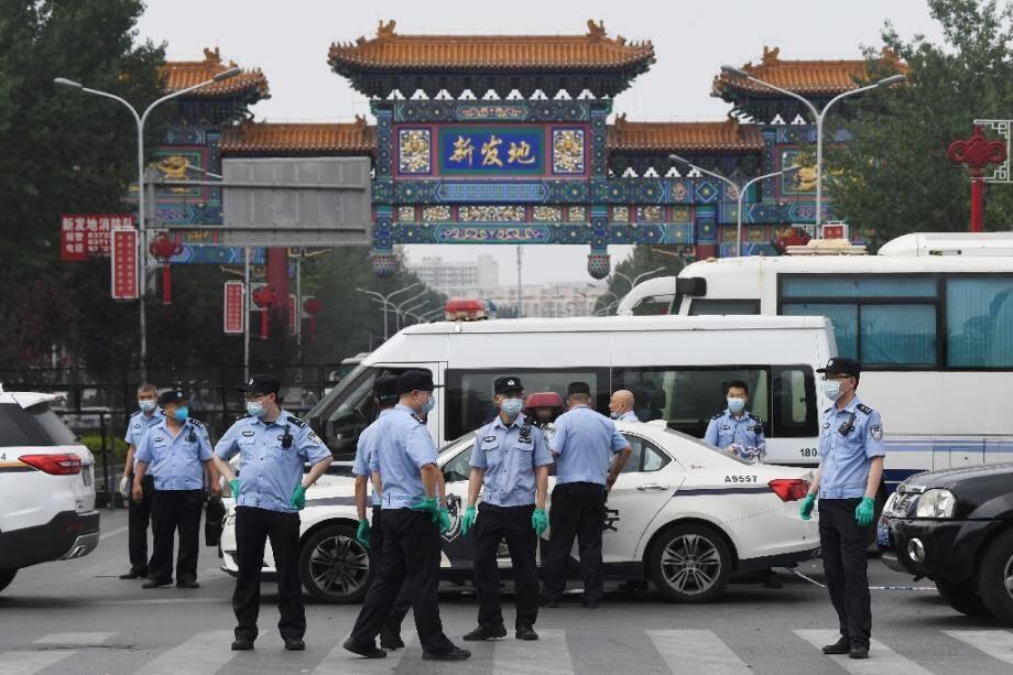 Des policiers chinois bloquent les accès au marché de Xinfadi où de nouveaux cas de coronavirus ont été détectés, le 13 juin 2020 à Pékin.