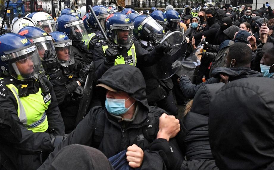 Des manifestants, certains équipés de masques, face à des policiers non loin de Downing Street le 6 juin 2020 lors d'une manifestation contre le racisme