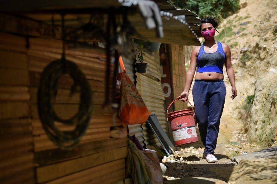 Yeimy Martinez porte un seau d'eau pour cuisiner, le 26 mai 2020 à Bogota, en Colombie