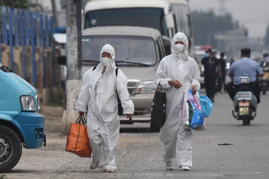 Deux Chinoises en combinaison intégrale de protection passent près du marché de Xinfadi, fermé après l'apparition de nouveaux cas de coronavirus, le 13 juin 2020 à Pékin