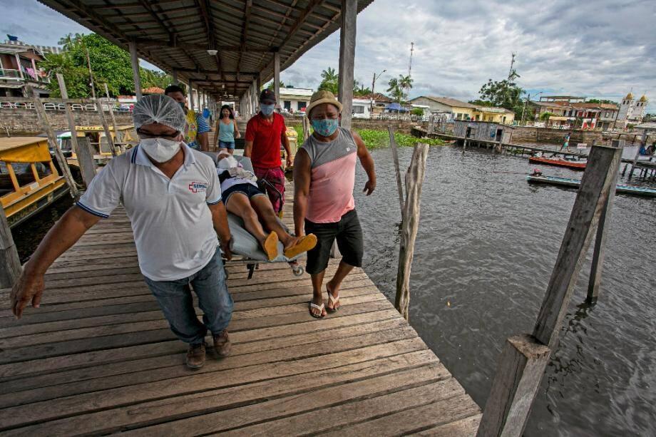 Un patient présentant des symptômes du coronavirus est porté sur un brancard avant son transfert pour un hôpital par voie fluviale, à Melgaço (Brésil), le 10 juin 2020