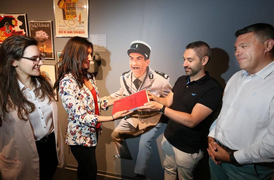 """Nora Ferreira, la directrice du musée De-Funès, remet le scénario annoté du film """"Le Gendarme et les gendarmettes"""" aux responsables du Musée de la gendarmerie de Melun, dans le cadre d'une exposition temporaire sur les gendarmes à l'écran."""