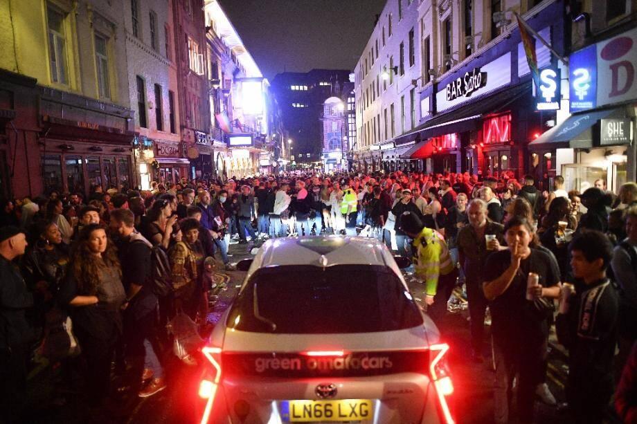 Une voiture tente de se frayer un chemin parmi les noctambules dans une rue du quartier de Soho à Londres, le 4 juillet 2020