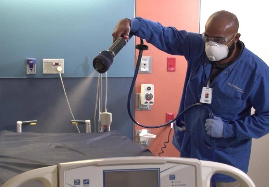 Photo fournie par Allied BioScience le 15 mai 2020 d'un homme appliquant l'antiviral développé par Allied BioScience pour tuer les virus sur les surfaces